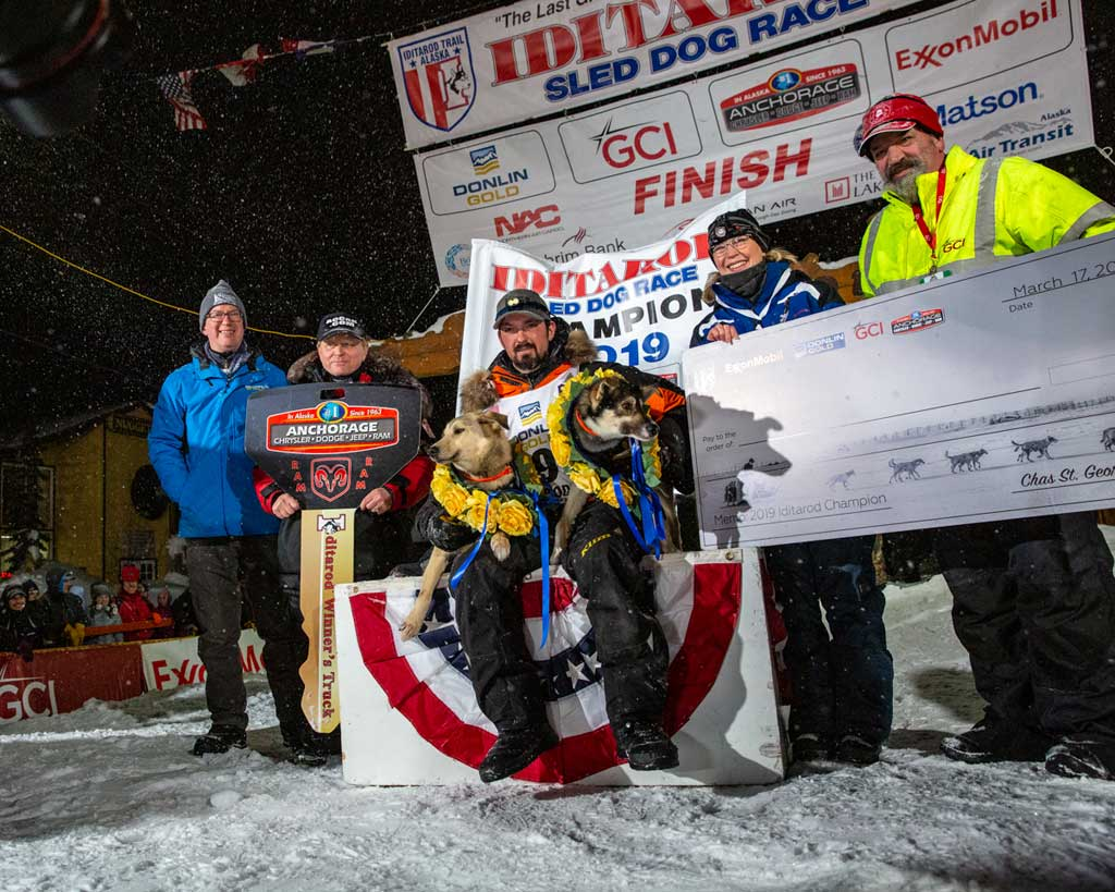 El veterano de la Iditarod Peter Kaiser (dorsal # 9), de Bethel, Alaska, cruzó en primer lugar bajo del arco en Nome.